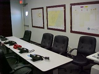 Tables, chairs, phones, and charts on the walls in the Emergency Coordination Center