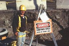 "Worker Standing Next to Sign which Reads ""Danger, Confined Space"""