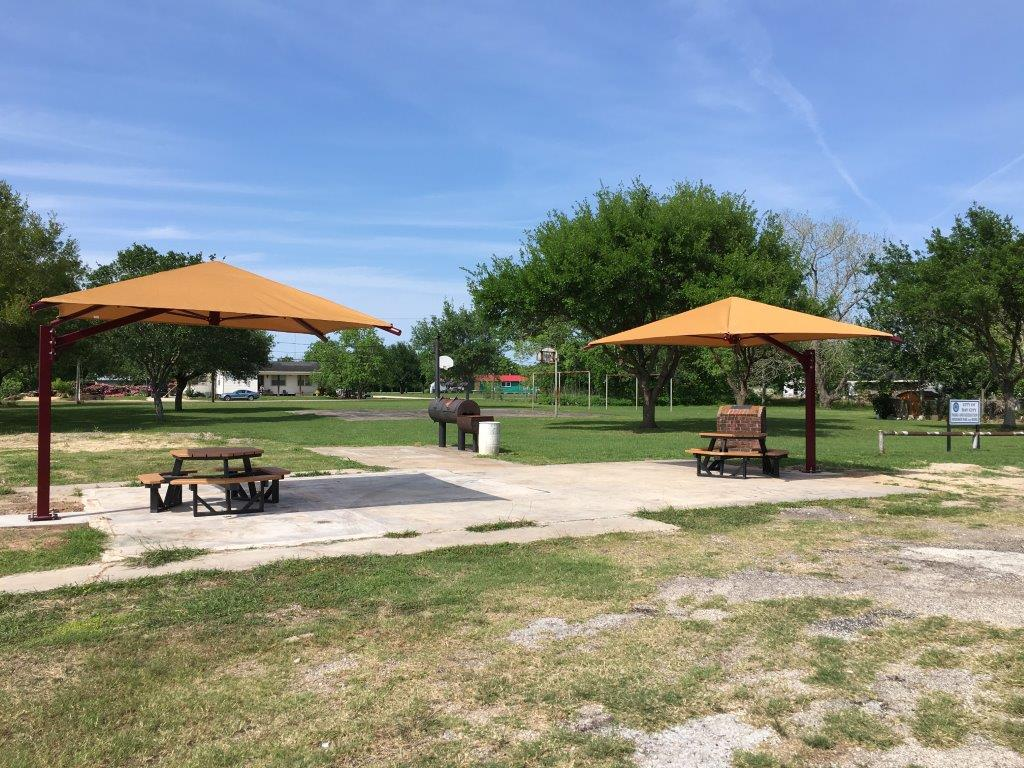 Two canopies over picnic tables near a grill